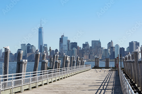 Empty pier and New York city skyline view with seagulls, sunlight Poster