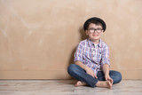 little boy on the floor in hat and glasses