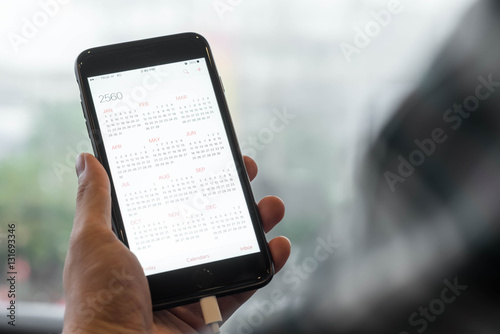 Poster Hand of man use smartphone show calendar of 2017 on screen