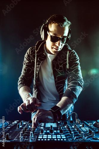 Poster DJ mixing music on mixer on dark background