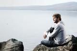 Giovane uomo seduto su una roccia