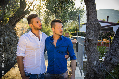 Poster Stylish handsome men walking on nice road. Gay couple outdoor