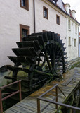 Large wheel churner with a wooden platform in front of it