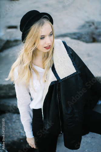 Poszter beautiful young blond woman standing on the rocks