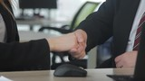 Business people shaking hands over a Desk. Office workers in business clothes. Travel on the slider in motion