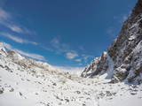 White snow, blue sky and rocky peaks. Nepalese severe winter. Nepal eco travel and extreme sport.