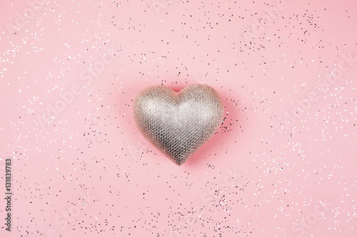 Silver heart on pink background with sparkles. © efetova