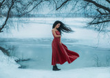 Beautiful young brunette woman flies with the birds. Background shore of a frozen river. . Sad face with a glimmer of hope to escape from the routine of everyday life. Fantasy photo, creative color