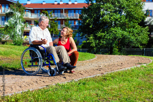 Poster man on wheelchair with young woman