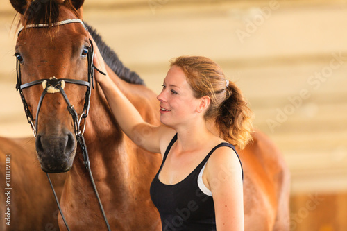Poster Jockey young girl petting and hugging brown horse