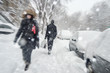 Snowstorm in Montreal. Pedestrians walking on sidewalk with motion blur