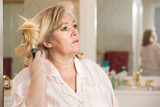 Mature womans morning routine - absentmindedly brushing her hair
