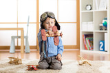 Child boy pretending to be pilot. Kid playing with toy airplanes at home. Travel and dream concept