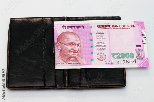 Poster New Indian currency of 2000 rupee notes into the money purse.