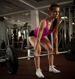 Woman workout in fitness gym with barbells - powerlift workout