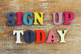 Sign up today written with colorful letters on rustic wooden surface