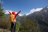 cheering young woman hiker open arms at the himalaya mountains