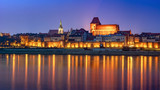 Torun at night, medieval Old Town reflected in Vistula river, Poland. Europe.