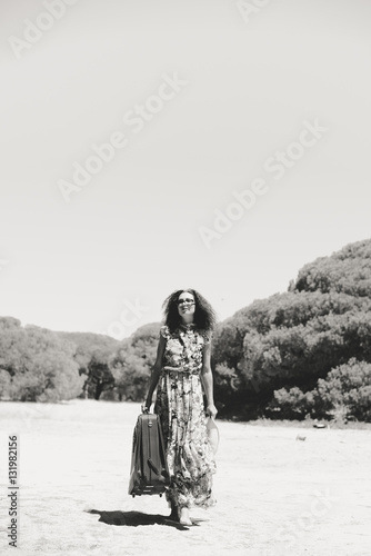 Poster Black and white image of beautiful elegant woman with suitcase walking nature ou