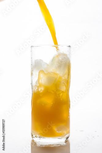 Poster Pouring Orange Juice to the ice glass