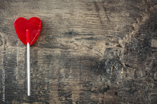 Red lollipop with heart shape on wooden background Poster