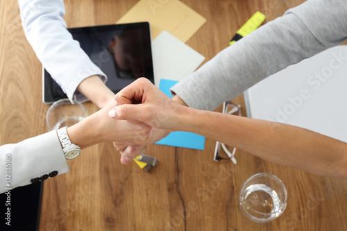 Motywacja, praca zespołowa nad projektem.Dłonie czterech osób w geście sukcesu, zwycięstwa