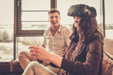 Cheerful couple having fun with VR in home interior
