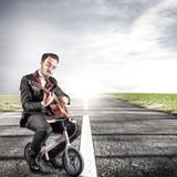 giovane manager che suona la chitarra in strada seduto su una piccola bici