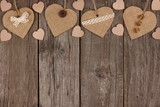 Top border of handmade burlap hearts with ribbon and buttons over a rustic wooden background