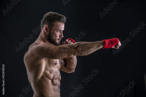 Young handsome topless boxer in red gloves looking at camera on black studio