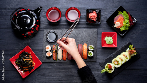Woman eating sushi with chopsticks top view