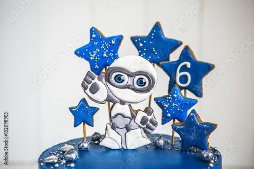 Торт космос синего цвета с пряниками в виде инопланетянина и звезд, и ягодами-планетами стоит на белом деревянном столе