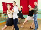 men and women having dancing class in studio