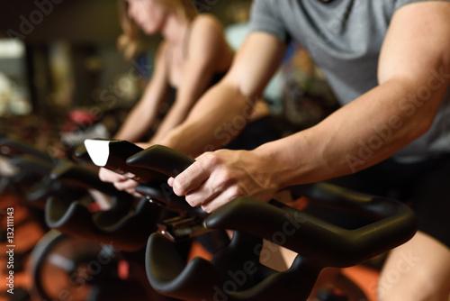 Sticker Couple in a spinning class wearing sportswear.