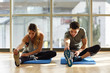 Leinwanddruck Bild - Two people streching their legs in gym.
