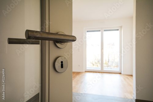 Leinwanddruck Bild Neubau-Immobilie Umzug in neue Wohnung - Tür in modernes Wohnzimmer
