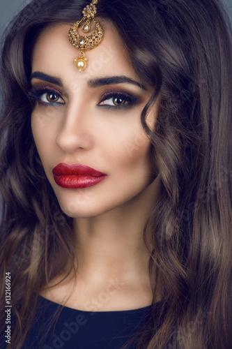 Poster Portrait of gorgeous young brunette with long hair and provocative make-up wearing precious Indian bridal hair accessories made of gold and purl