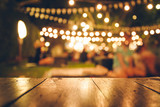 Fototapety Image of wooden table in front of abstract blurred restaurant lights background