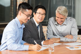 Smiling Asian business people closing deal