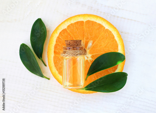 Plakat Bottle of essential aroma oil on orange slice, fresh leaves, white wooden table background, top view