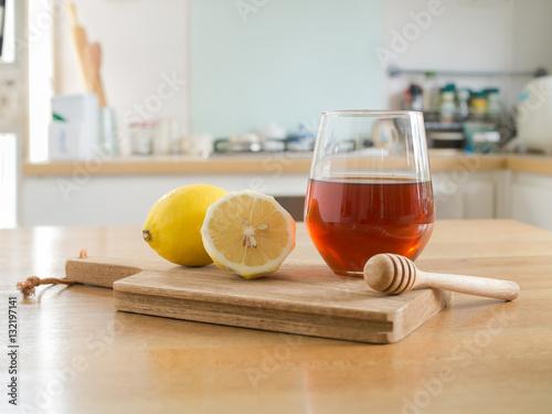 Poster Honey lemon - lemon on chopping board and Glass of honey and honey dipper on woo