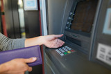 close up of hands withdrawing cash at atm machine