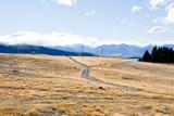 秋のテカポ湖畔の牧草地の中の道(ニュージーランド)