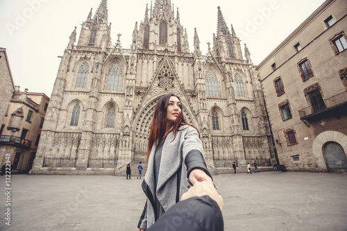 Lovers couple holding hands in a Cathedral Holy Cross and Saint Eulalia. Europa, Barselona, Spain. Old Building in Barcelona, Spain