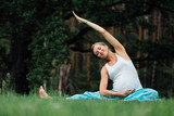 pregnant yoga prenatal maternity doing different exercises. in park on the grass, breathing, stretching, statics.