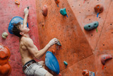 Muscular and fit shirtless man exercise bouldering and climbing indoor at artificial wall