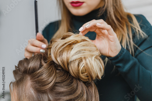 Poster Hairdresser makes upper bun hairstyle close-up on brown hair of beautiful woman