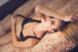Attractive blonde woman in black lingerie posing on her bed