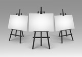 Set of Black Wooden Easels with Mock Up Empty Blank Canvases Isolated on Background