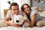 Joyful delighted man holding a fluffy bear